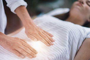 Female therapist performing Reiki therap