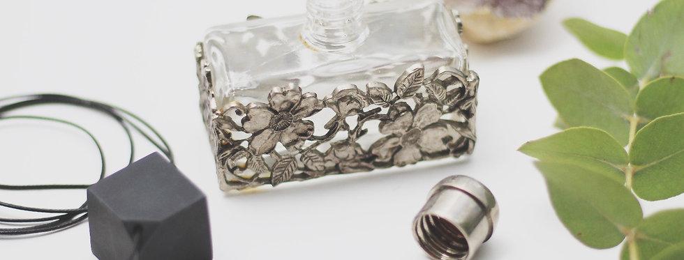 Vintage glas perfume bottle in a tin flower coat