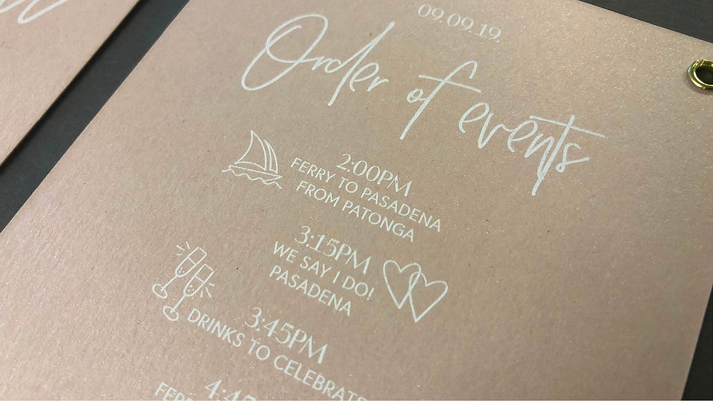 Photo of a white printed wedding invitation on a nude coloured metallic paper.