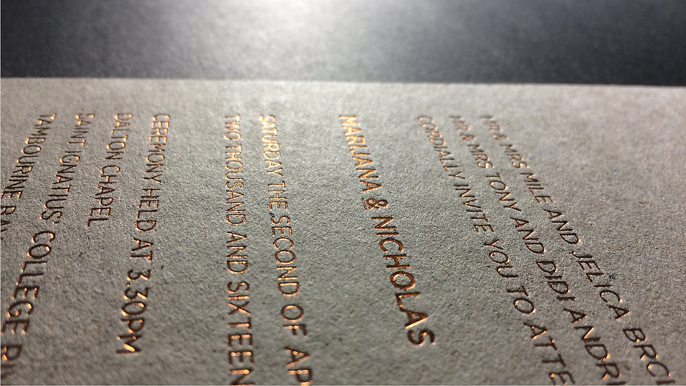 The reverse face of a rose gold foiled wedding invitation featuring foiled type.