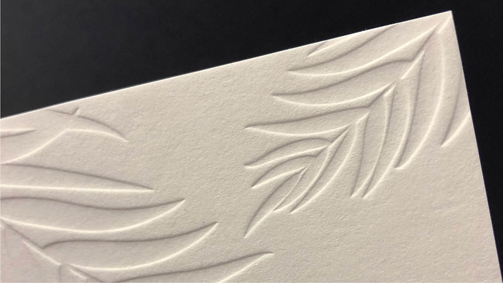 Photo of a wedding invitation for Jayme and Patrick featuring a blind letterpress print for the palm fronds
