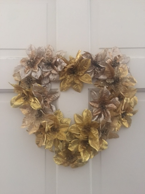 gold with light gold poinsettias in the shape of a heart this wreath is very full of poinsettias and festive looks lovely on a front door
