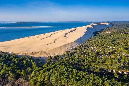 Plus haute d'Europe et monument naturel exceptionnel, la Dune du Pilat attire chaque année des milliers de visiteurs. Elle est l'un des lieux incontournables à visiter en Gironde, et un arrêt inévitable pour les voyageurs.  Au cœur du splendide bassin d'Arcachon, elle vous emmène à la découverte d'un fabuleux cadre sauvage. Vous pourrez d'ailleurs admirer la magnifique réserve régionale des Landes de Gascogne, ainsi que la région bordelaise.