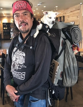 man with small white dog on backpack - C