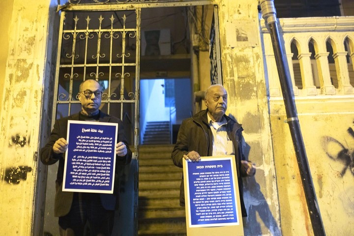 Two men of the Sabagh family stand outside the stairs of their old home holding signs telling their family story