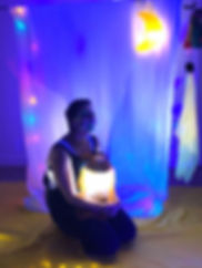 a girl sitiing on the floor with a light