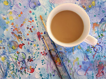 a cup of coffee on a top of a watercolor painting