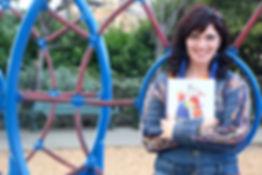 Julia Kosivchuk at the playground holding the book