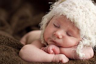 Newborn Baby Sleeping with furry hat on head