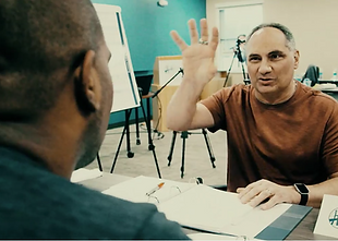 Joe Battista talking with a colleague in a classroom