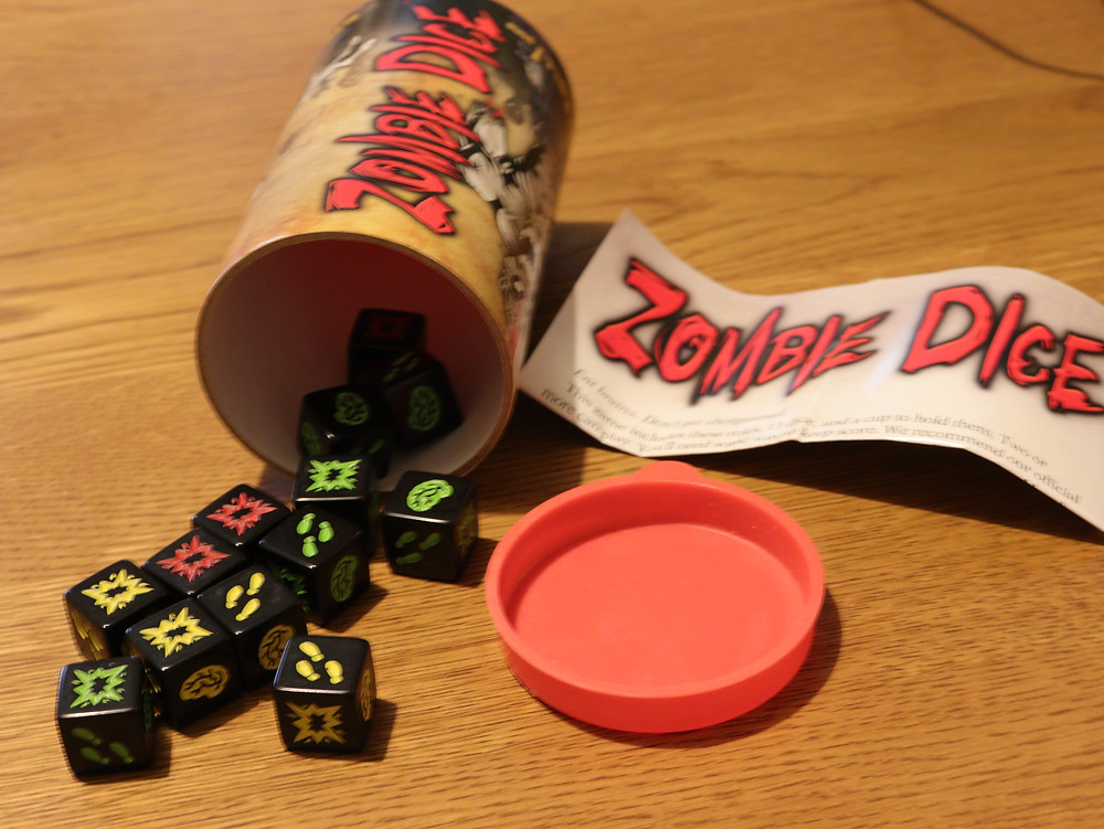 The game Zombie dice spilling out of the game box onto a wooden table showing the dice and the rules pamphlet