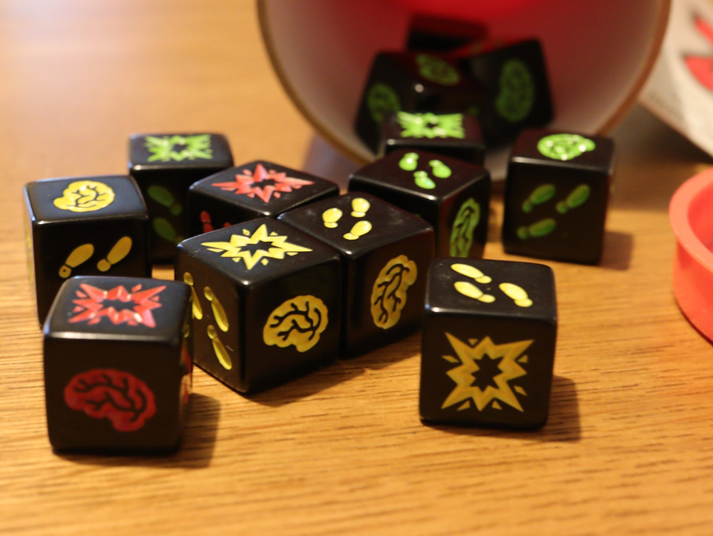 A close-up of the dice from Zombie Dice spilling out of the game box.