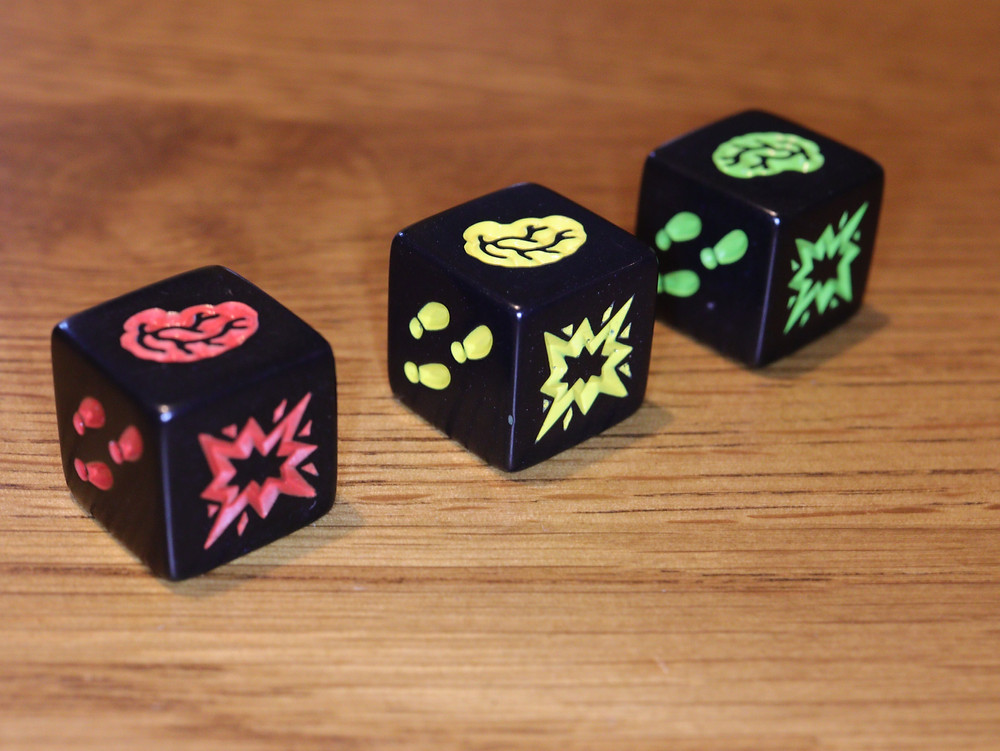 An example of each of the three colours dice in the game Zombie Dice showing each of the three unique die faces: footsteps, a blast symbol, and a brain .