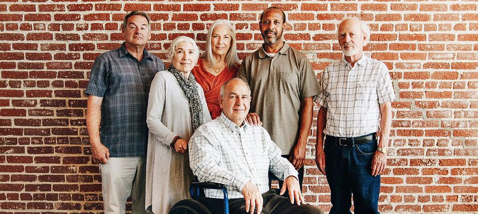 happy-elderly-man-on-a-wheelchair-with-friends-9XVTRTS.jpg
