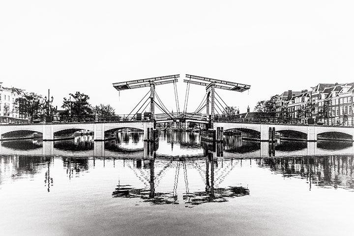 De magere brug vanaf het water vlak na zonsopkomst.