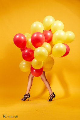 Fashion black high heels in studio with red and yellow balloons