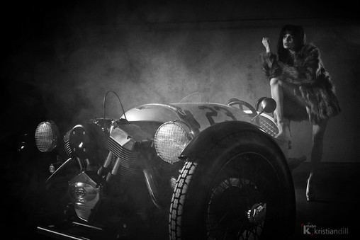 Morgan black and white 3 wheels car with fashion sexy woman in fake fur and high heels