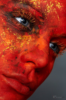 Woman red facepainting with blue eyes