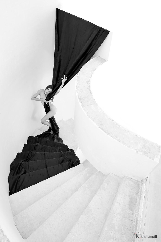 Nu minimaliste avec tissu noir dans les escaliers