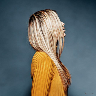Woman studio artistic portrait with long blond hair and yellow shirt