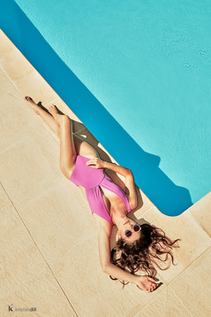 Woman with pink swimwear by the swimming pool