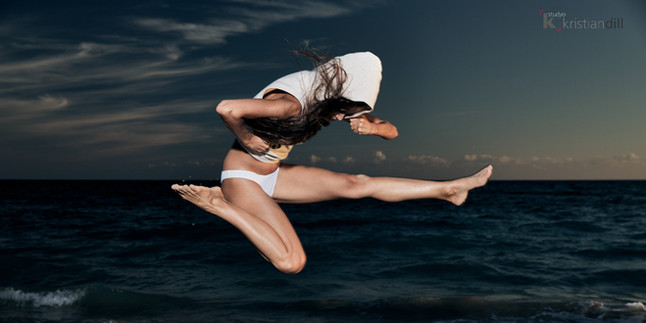 Sport jump woman on the beach at sunset in Italy