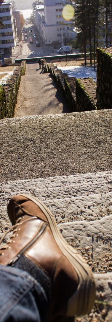 Harjun portaat kevätauringossa, etualalla valokuvaajan jalka.