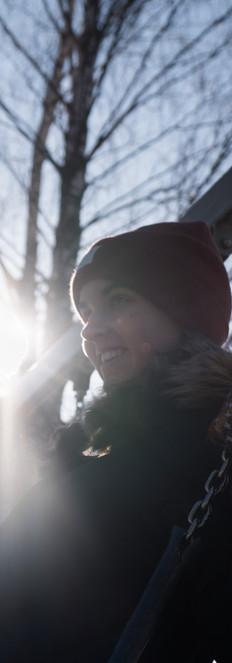 Hymyilevä tyttö keinussa, punainen pipo päässä, taustalla paistaa aurinko.