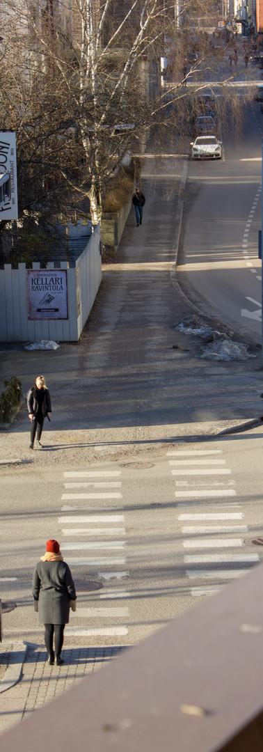 Autotien ylittävä risteys, jossa molemmin puolin seisovat hahmot odottavat valon vaihtumista.