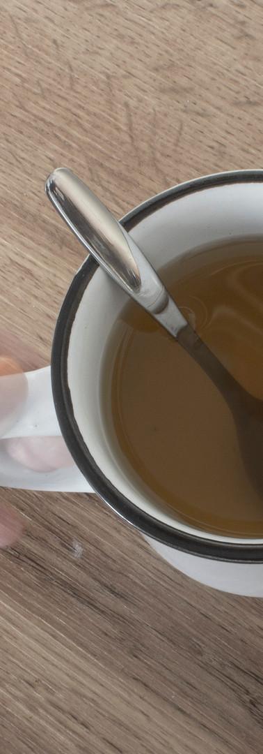 Osittain läpikuultavan hahmon käsi pitelemässä teekupin kahvasta kiinni.