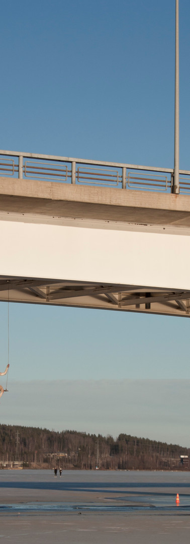 Kuokkalan silta, jonka alla roikkuva keinuvaa hahmoa esittävä tilataideteos.