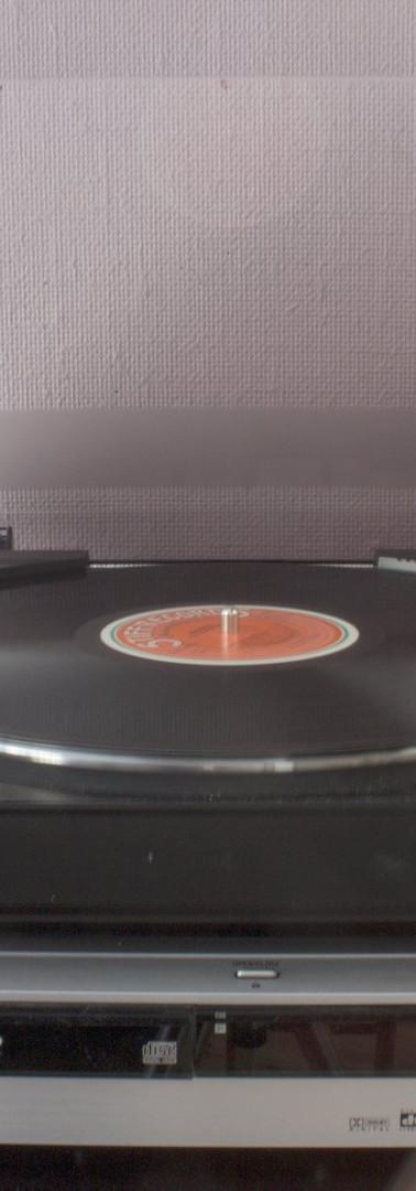 Osittain läpikuultavan hahmon kädet siirtämässä vinyylisoittimen neulaa levylle.