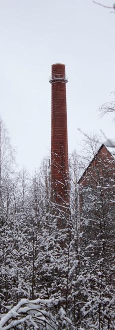 Lumisen latvuston takaa nouseva tehtaan piippu.