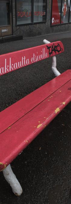 """Punainen puiston penkki, jossa teksti """"rakkautta etsiville"""", sekä graffiteja."""