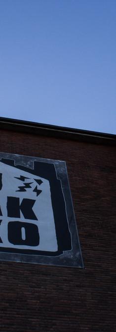 Tanssisali Lutakon seinä, jossa iso Lutakon logoa esittävä seinämaalaus
