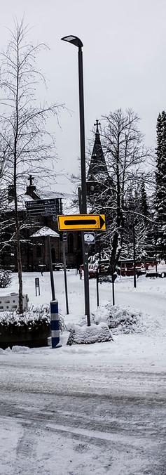 Luminen kirkkopuisto ja sen ympärillä kävelyteitä pitkin käveleviä vanhoja ihmisiä.