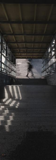 Symmetrinen kuva rappusista, joiden päässä varjon jälkeensä jättävä kävelevä hahmo.