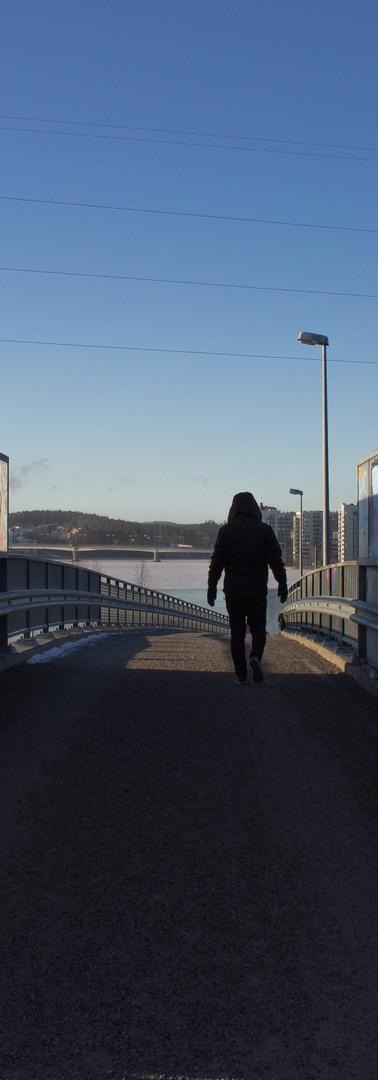 Kävelysiltaa pois päin kävelevä hahmo, jonka molemmilla sivuilla olevissa seinämissä värikkäitä graffiteja.