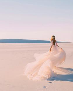 La mariée en robe légère court sur les dunes de sable