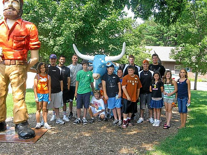 15 people posing next to statue of babe the blue ox smiling at camera