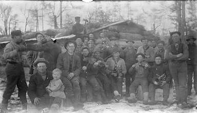 old logging photo, black and white, logging crew gathered outside in front of cabin