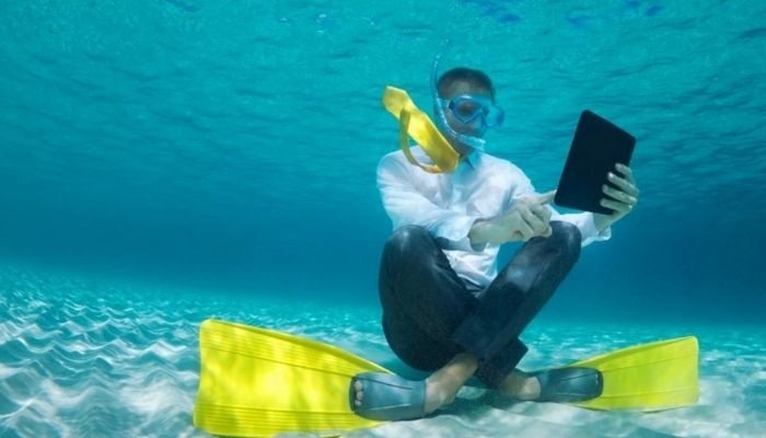business man under water in scuba diving gear in a suite with ipad