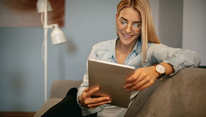 Woman in glasses holding ipad wearing a watch sitting on a sofa reading