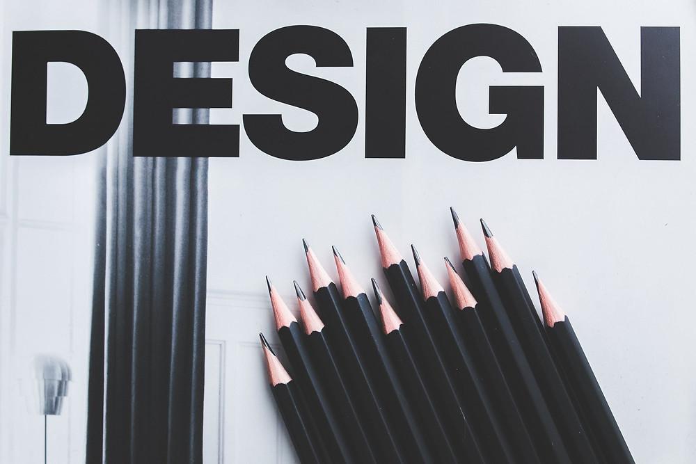 """Black pencils over a sheet of paper, titled """"design""""."""