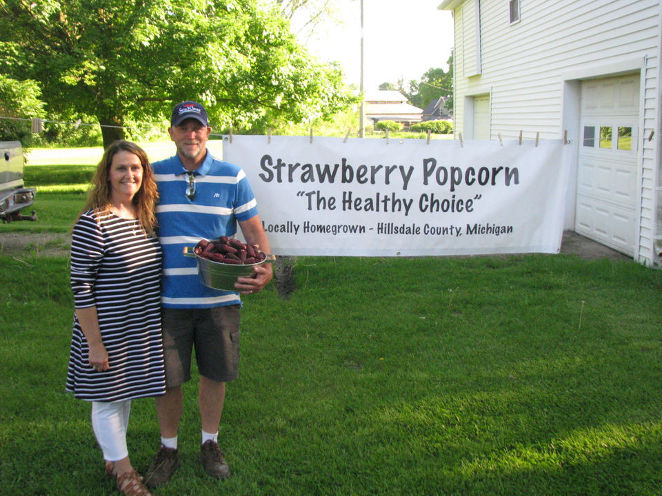 Couple standing in front of a banner with a basket of strawberry popcorn