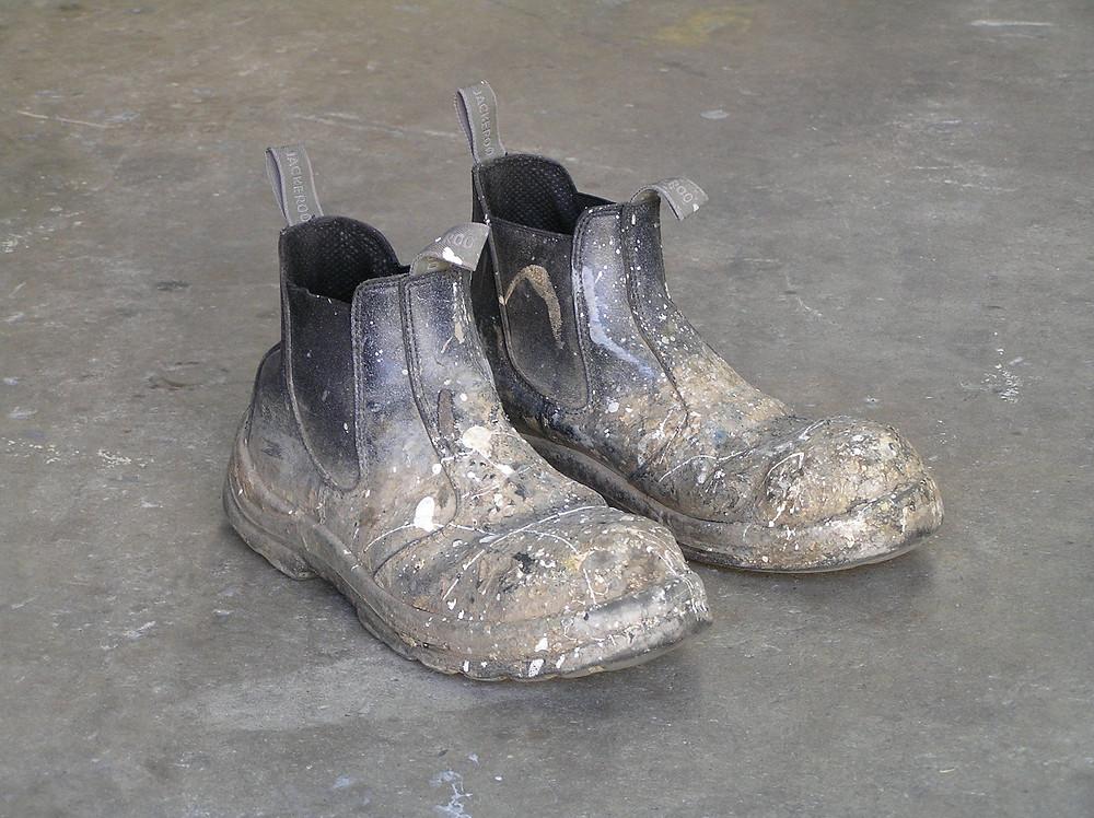 Construction boots on concrete slap with paint splatters