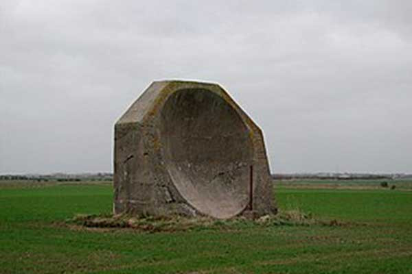 """4.5-metre-high (14 ft 9 in) WW1 concrete acoustic mirror near Kilnsea Grange, East Yorkshire, UK. The pipe which held the """"collector head"""" (microphone) can be seen in front of the structure"""