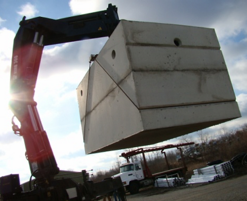 large crane lifting a concrete septic tank