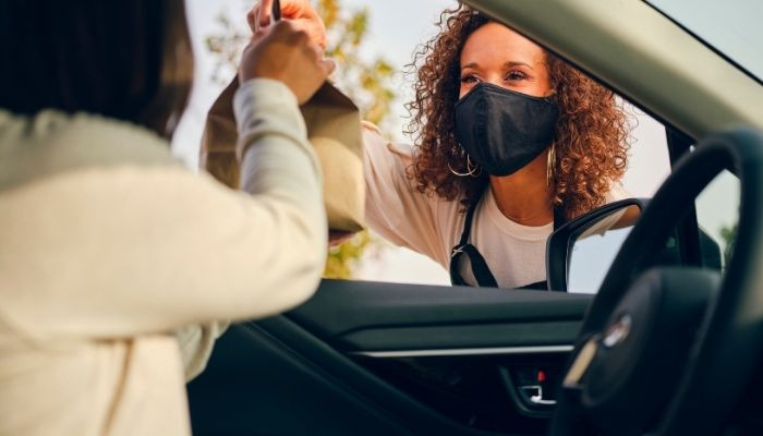 women in car picking up curbside order during pandemic