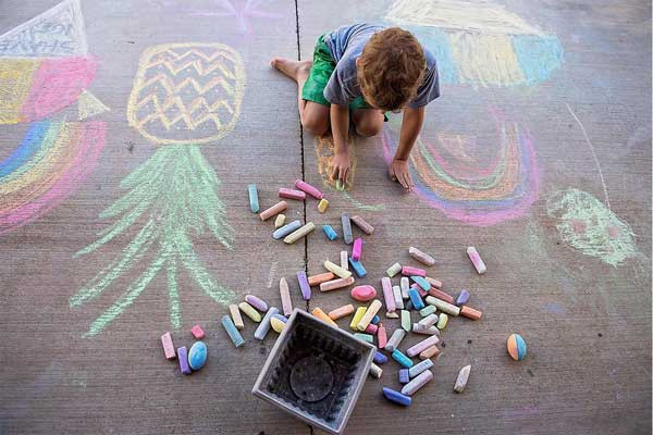 Young child drawing on sidewalk with chalk in the warm weather